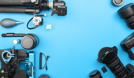 Digital camera with lenses and equipment of the professional photographer on blue paper background