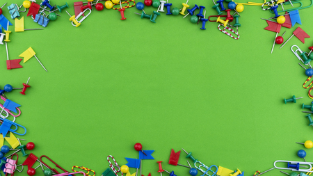 Set of colorful color push pins Thumbtacks frame top view isolated on green background Stock Photo