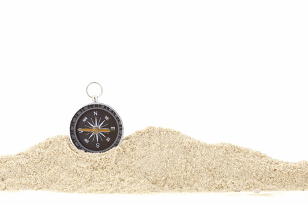 compass on the pile sand ,white background copy space for text.