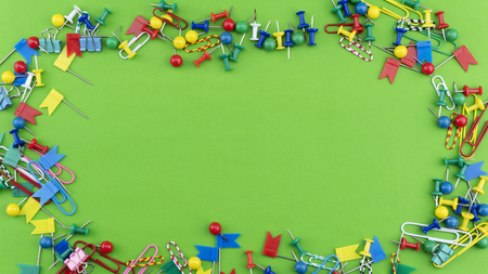 Set of colorful color push pins Thumbtacks frame top view isolated on green background.