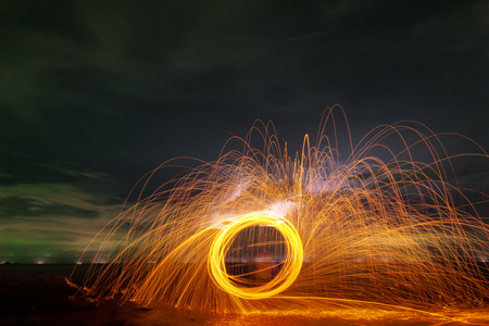 Swing fire Swirl steel wool light photography over the stone with reflex in the water long exposure speed motion style.