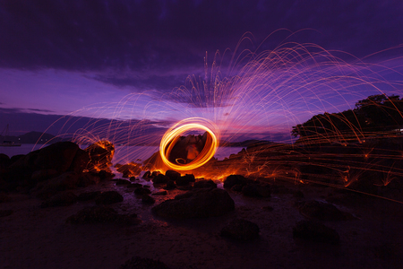 Swing fire Swirl steel wool light photography over the stone with reflex in the water Beautiful light in the sunrise or sunset time, long exposure speed motion style.