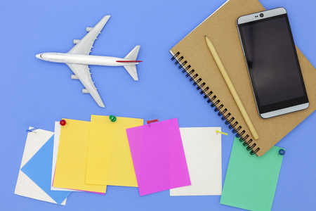 Airplane model with smartphone and paper note on blue background. Standard-Bild
