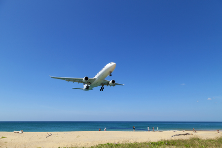 Commercial airplane landing above sea and clear blue sky over beautiful scenery nature background,concept business travel and transportation background.