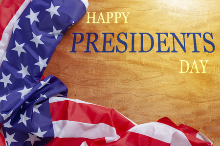 Happy Presidents Day text on wooden with flag of the United States Border.