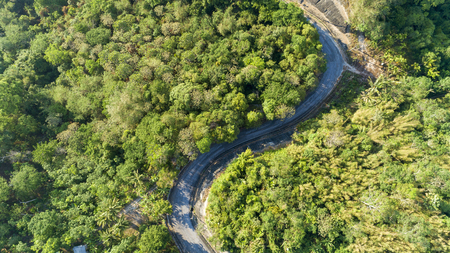 Asphalt road curve in high mountain image by Drone bird's eye view. Фото со стока