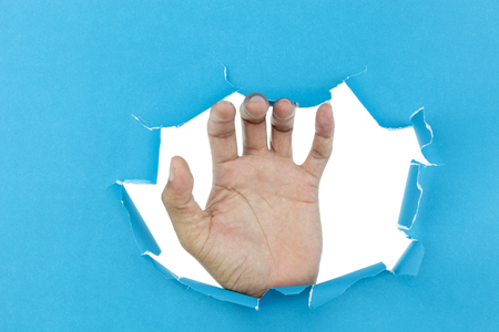 male hand ripped blue paper on white background,space for your message on torn paper.