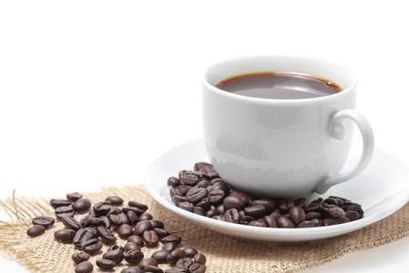 Tasse à café et grains de café sur fond blanc.