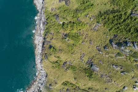 Tropical sea with wave crashing on seashore and mountain aerial view drone top down view.