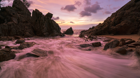 Long exposure image of Dramatic sky seascape with rock in sunset scenery background. Фото со стока