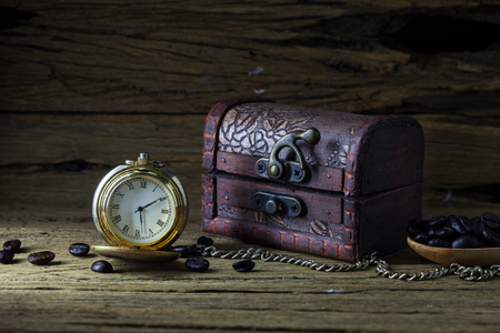 Old pocket watch and Treasure Chest on dark wood, still life.