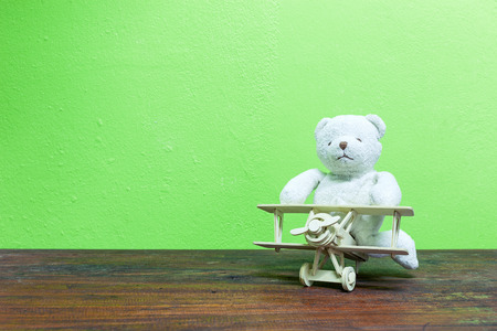Teddy bear ride Wood airplane on old wood and green wall background.