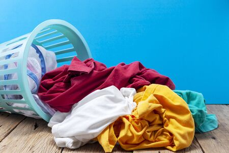 Pile of dirty laundry in washing basket on wooden,blue background.