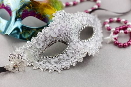 A festive,Beautiful white mardi gras or carnival mask on beautiful colorful paper background.