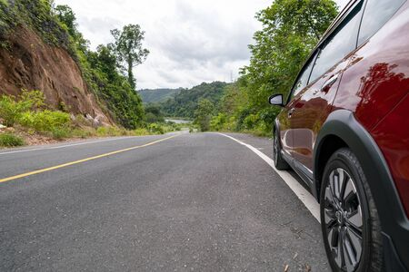 Red Suv car on Asphalt road with mountain green forest Transportation to travel concept.