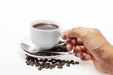 Male hand holding white coffee cup and coffee beans on white background. Stock Photo