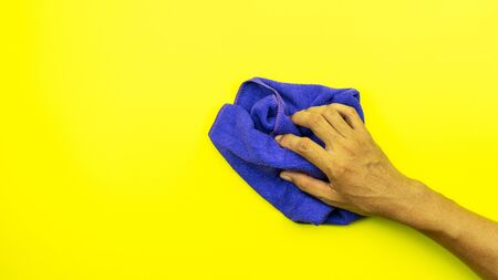 Man hand holding blue microfiber cleaning cloth isolated on yellow background