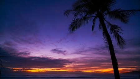 Beautiful sunset or sunrise with silhouette palm tree on tropical island