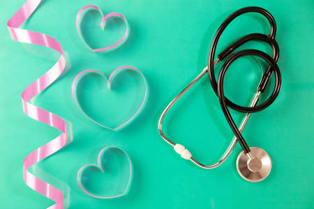 Stethoscope with heart ribbon on green paper background Stock Photo