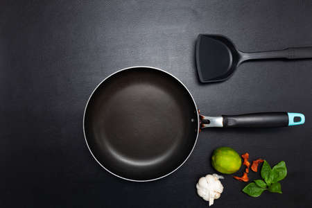 Cooking background Top view frying pan and pot on black leather table background Archivio Fotografico