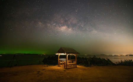 Landscape seascape Nature view image of Amazing Milky Way galaxy over sea with Bamboo hut in the foreground in Night sky at Phuket Thailand.