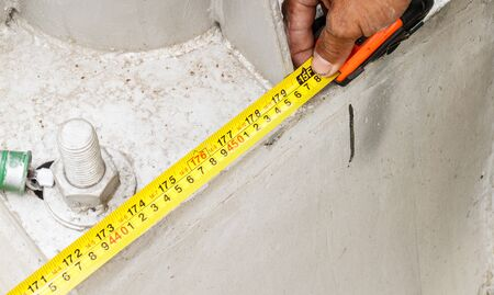 Man measuring with measure tape at construction site Stock Photo