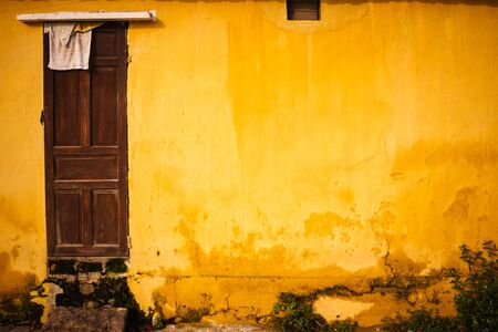 Old and grungy yellow wall with wooden door