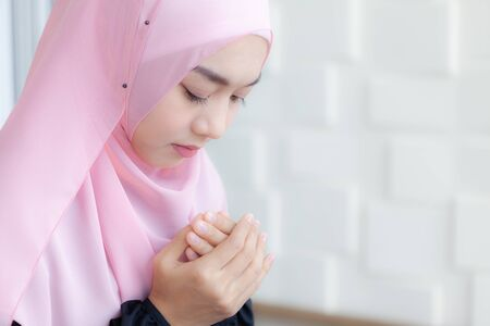 Young Asian Muslim Women Praying to Allah in peace, wearing a pink hijab.