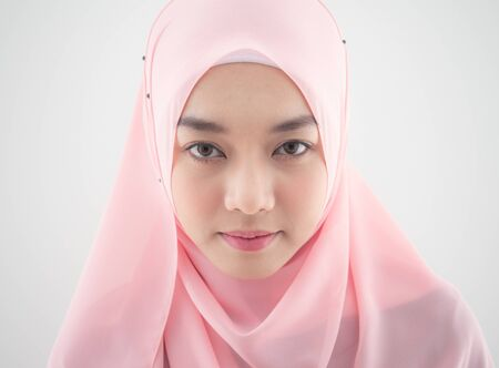 Close up Portrait of a beautiful Muslim Asian woman in a pink hijab on white background. Stock Photo