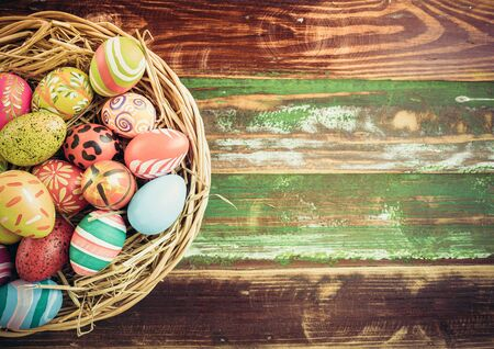 Easter eggs in various patterns and colors in a bird's nest placed on a wooden floor decorated in retro style.