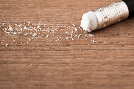 Closeup pencil eraser on wooden table, soft focus