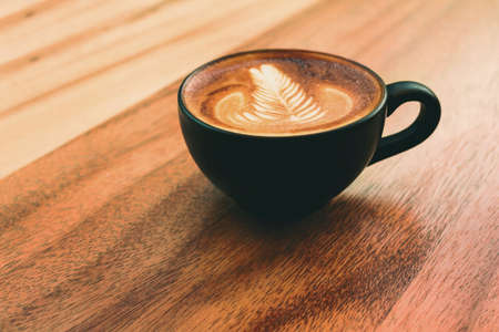 Coffee mug of Latte art coffee breakfast on wood  table  in morning time with light from window  vintage cafe style
