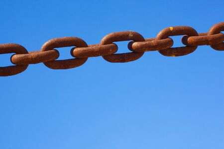 grunge rusty chain closeup over the blue clear sky Stock Photo