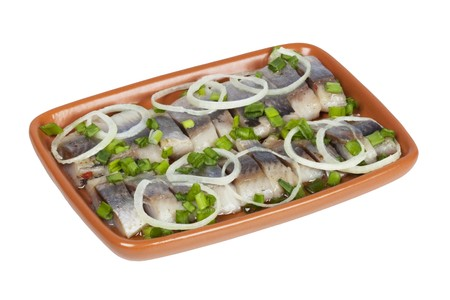 salted herring in oil with onion and green chives on the brown plate  image isolated on a white background