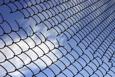 no boundaries: The fence of broken wire netting on the background of blue sky Stock Photo