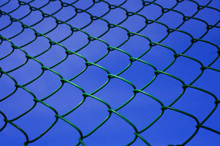 chainlink fence against the background of blue sky photo