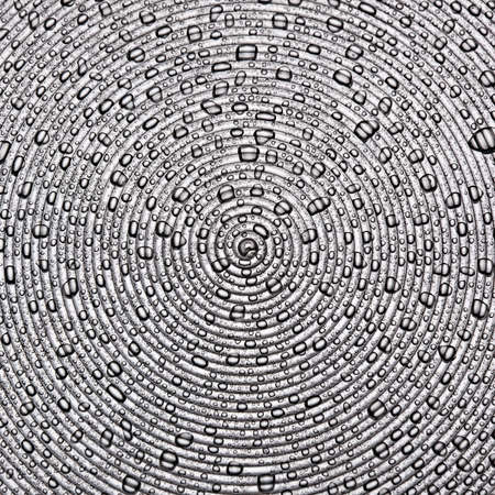 water droplets on a  surface of concentric circles studio shot photo
