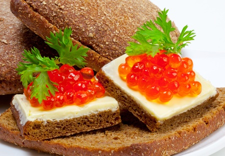 appetizer with red caviar and butter on bread photo