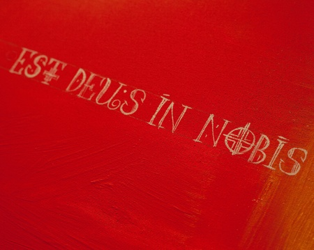 est: Latin phrase Est deus in nobis means God is in us - letters on a red background
