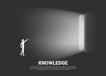Silhouette of businessman point to light from open book. Concept of knowledge of book