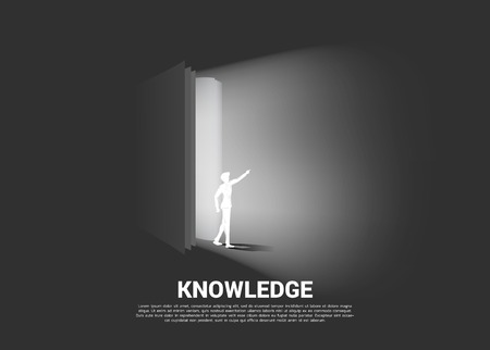 Silhouette of businessman walking from open book. Concept of knowledge of book