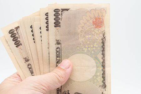 Close up hand hold japanese currency yen money banknote. Background concept for japan economy.