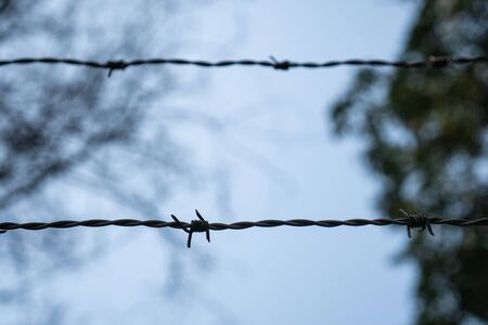 Shallow Depth of field of barbed wire and blurred background. Concept for forbidden area and security.