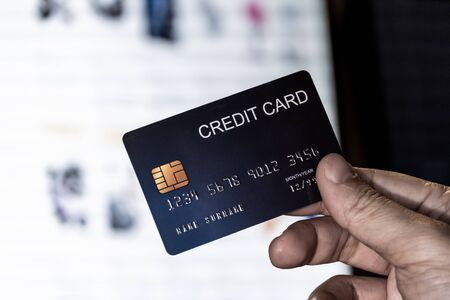 Credit card in hand with online shopping website monitor background. Concept for technology and e-commerce.