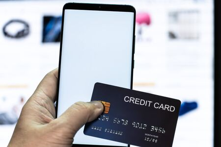 Mock up mobile phone and credit card in hand with monitor background. Concept for mobile application technology and online e-commerce. Stock Photo