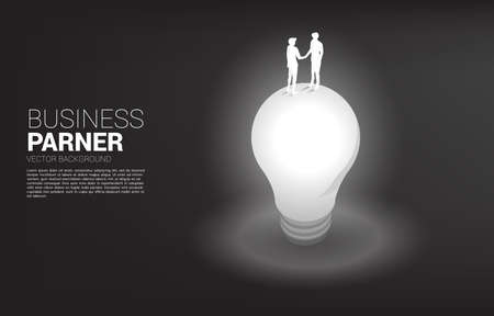 Silhouette of businessman handshake top top of light bulb. Concept of team work partnership and cooperation.