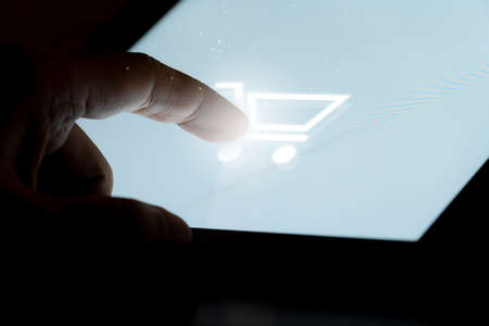Finger touch on shopping cart on Tablet screen Mock up with light. Concept for mobile phone technology and e-commerce.