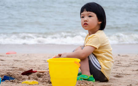 3 years old asian kid play sand on the beach. Background for family life and education. holiday with children. Stock fotó