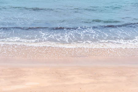 Close up ocean wave bubble on sandy beach. Background for vacation holiday and natural feeling.