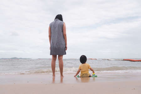Mother and 3 years old asian kid playing on the beach. Background for family vacation and recreation. 版權商用圖片